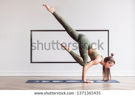 Slim charming young girl gymnast doing a complex handstand on the mat on the floor in a gymnastic suit. Concept of yoga and acrobatics. Advertising space