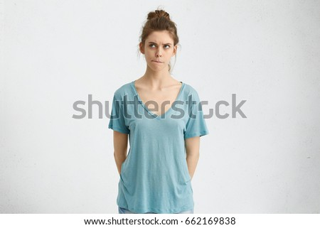 Slim college student in blue T-shirt having hair bun holding her hands behind, biting her lips looking aside with dreamy expression having something in her thoughts. Woman contemplating attentively