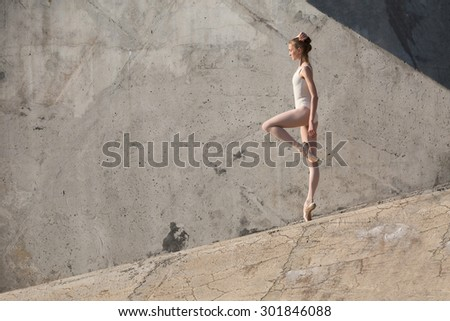 Slim dancer stands in a ballet pose and looking down on a gray urban concrete background. Outdoors shooting with sun light.