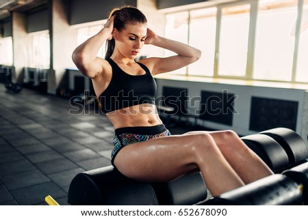 Slim female athlete trains press in sport gym