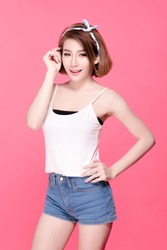Slim fit body of asian woman akimbo arms and touch her face, pink background