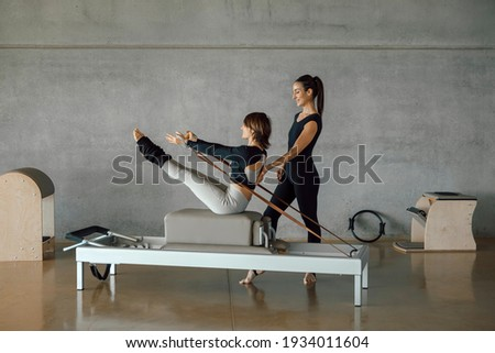 Slim fit Woman doing core exercises while taking Personal Pilates lesson on a Reformer machine, by a female instructor at a big gymnasium center, wide industrial studio. Healthy fitness lifestyle. Stock photo ©