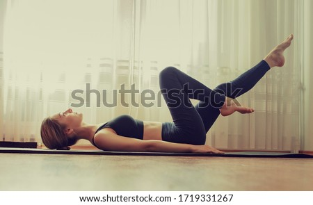 Slim fitness young girl practices relaxation yoga indoor at home.  Sport, healthy lifestyle.