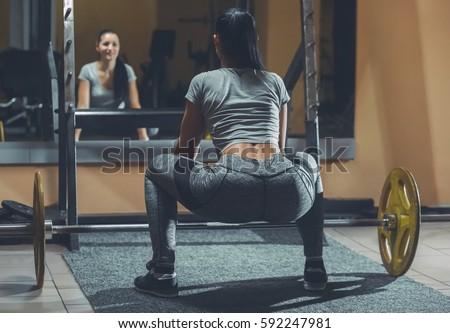 Slim girl bodybuilder lifting heavy barbell standing in front of the mirror while training in the gym. Sports concept, fat burning and a healthy lifestyle.
