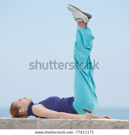 Slim girl does morning exercises. Attractive young woman  lying down on back