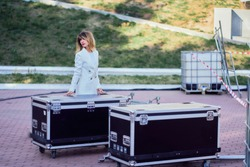 slim girl in a white coat  standing next to a flightcase with equipment. Preparing the stage for a concert in the open air.