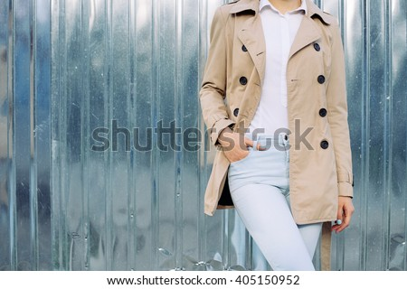 Slim girl in jeans, a beige coat and white shirt outdoors in spring, copy space. Stock photo ©