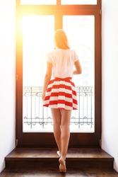 Slim girl in short skirt holding knob of the door to the balcony
