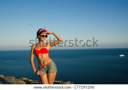 slim girl in swimsuit on the background of sky