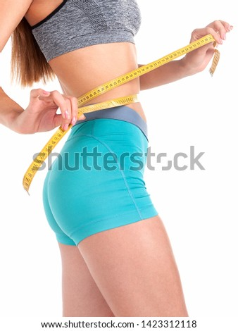 Slim girl in turquoise shorts measures waist size with a tape. Slimming Diet. #1423312118