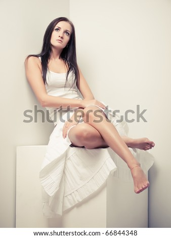 Slim girl in white top and skirt posing in a studio