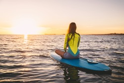 Slim girl on stand up paddle board on a quiet sea with summer sunset colors. Relaxing in ocean