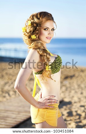 Slim girl resting at the beach - happy smiling woman enjoying summer sun. Romantic woman in swimwear relaxing at vacation holidays near the sea. Beautiful blonde bikini model at exotic spa resort
