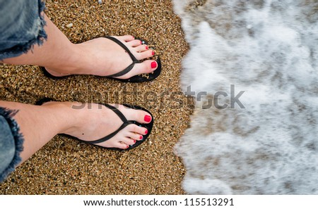 slim girl's legs on sandy beach