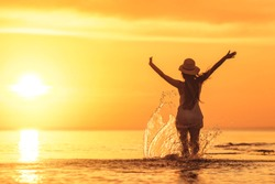 Slim girl's silhouette with raised arms against beautiful sunset at tranquil sea beach
