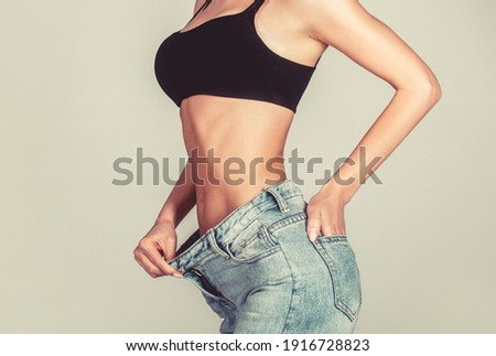 Slim girl wearing oversized pants. Woman shows weight loss. Dieting. Woman showing slim body after sport trainings, healthy eating. Weight loss concept. Thin woman in big pants, weight loss concepts.