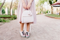 Slim girl wearing trendy pastel shoes posing in park during walk in morning, carrying stylish backpack. Lady in long purple gown holding cute bag in hands standing on blur background.