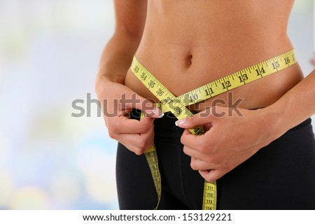 Slim girl with centimeter isolated on white #153129221