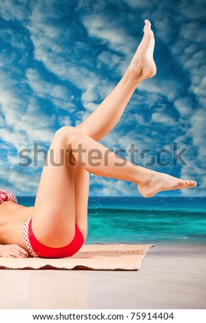 slim legs of a woman lying on beach