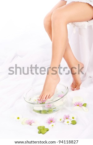 Slim legs of beautiful girl with aromatherapy bowl
