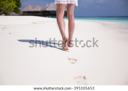 Slim legs walking on beautiful sand beach. Woman leaving footprints on the white sand. Closeup detail of female feet and waves of blue ocean on sand. Maldives.  #395105653