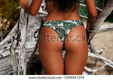 Slim luxury girl in a black bikini on the beach. Photos from behind. Perfect tanned body, sexy ass, perfect figure. Rest on a tropical island. Golden bracelets. Glamour. Photo in low key #1098887294