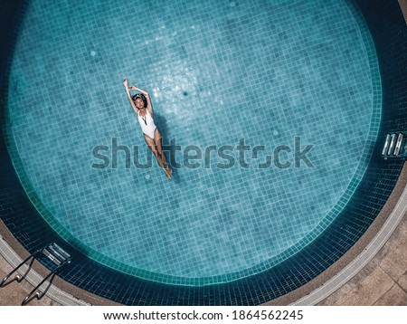 Photo of  Slim meditative lady floats  in the round blue pool of a tropical hotel,  her arms up, flecks in the clean water. Fashion concept, drone view