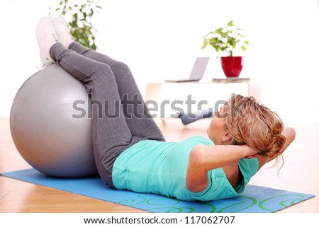 slim mid aged woman do her exercises with abs ball at home