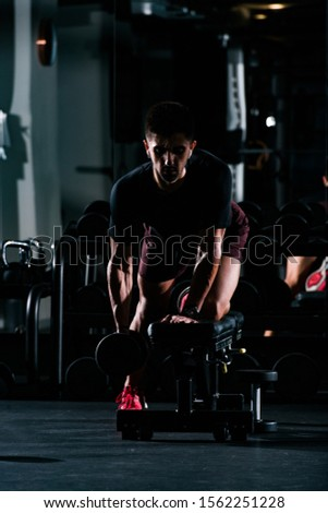Slim muscular young man lifting weights in the gym and listening to music on the headphones, high contrast image