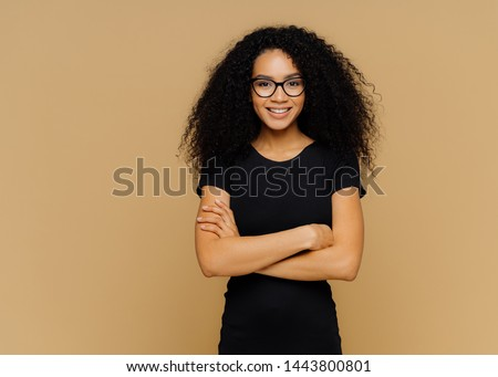 Slim satisfied woman with Afro haircut, wears black casual clothes, optical glasses, has confident expression, listens interlocutor, isolated on beige background. Cute teenage girl enjoys life.