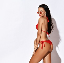Slim sexy tanned brunette woman posing in stylish red beach bikini and sunglasses on white background with copy space. Summer vibes. Hot summer beach swimsuits.