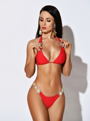 Slim sexy tanned brunette woman posing in stylish red beach bikini on white background with copy space. Summer vibes. Hot summer beach swimsuits.