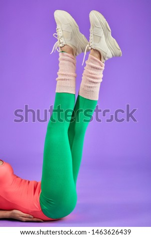 slim sporty body in pink bodysuit and legs raised up in green leggins and white sport shoes, making cross moves in air on light violet background. Studio shot, sport and fitness concept