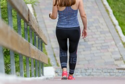 Slim sporty woman descending the stairs outdoor. Healthy lifestyle background