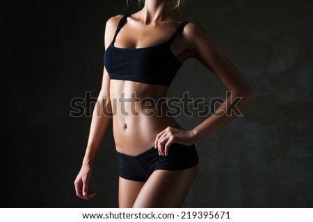Slim tanned woman\'s body  over dark grey background