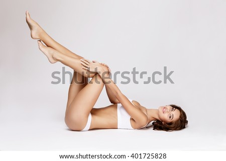 Slim tanned woman\'s body over gray background