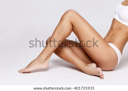 Slim tanned woman's body over gray background #401725933