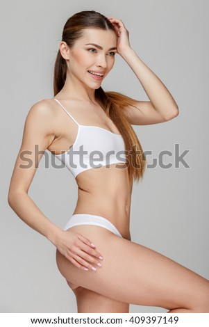 Slim tanned woman's body over gray background #409397149