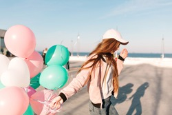 Slim trendy girl in stylish pink clothes walking along the ocean wharf enjoying windy morning in weekend. Charming young long-haired woman running at the sea pier waving bunch of party balloons