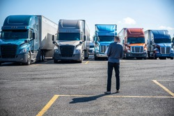 Slim Truck driver carries a box with purchases in his hands and going to his big rig semi ruck parked on the truck stop parking lot standing in row with another semi trucks with semi trailers
