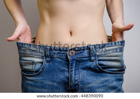 Slim Waist of Young Woman thin body with perfect, showing her jeans after successful diet or fitness, Weight loss and slimming concept.