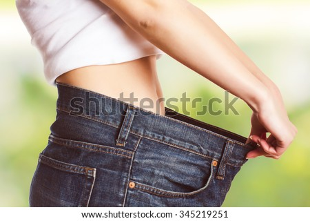 Slim Waist of Young Woman with perfect healthy thin body,showing her old jeans after successful diet. .Weight loss and slimming concept.