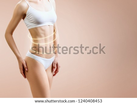 Slim woman body with glowing circles shows lifting effect. Over beige background. #1240408453