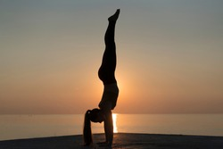 Slim woman doing yoga on the sunset. Silhouette of a girl standing on her hands for power exercise. Yoga coach practicing handstanding on the pier. Concept of healthy lifestyle and sport outdoors.