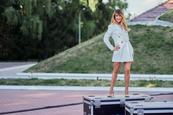 slim woman in a white coat  standing next to a flightcase with equipment. Preparing the stage for a concert in the open air. copy space