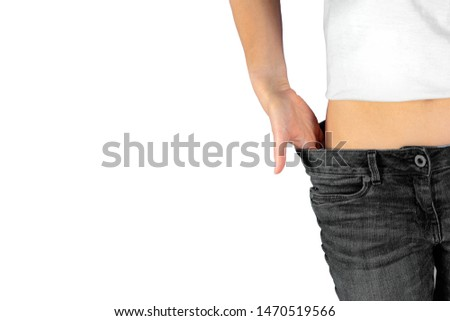 Slim woman in jeans after losing weight isolated on white background. Authentic photo