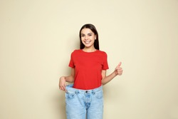 Slim woman in oversized jeans on color background. Weight loss