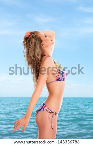 Slim woman posing in front of sea water at beach