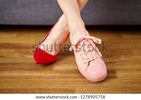 Slim woman's legs in two different shoes with red high heels and coral sneakers on gray couch background. #1278905758