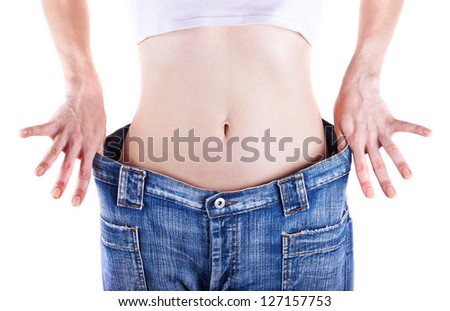 Slim woman shows her weight loss by wearing an jeans, isolated on white background